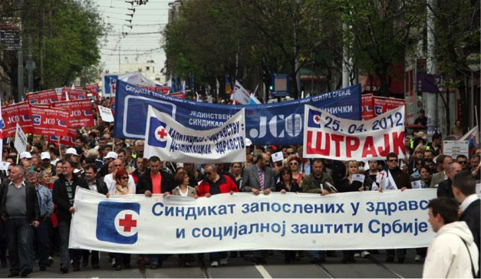 "IMAGE DESCRIPTION: In April of 2012, trade unions of health and social protection workers in Belgrade, Serbia, organized a one-hour ""warning strike"" in response to a state proposal to reduce the salaries of all healthcare employees by 10 percent. In this image, a dense crowd or professionally dressed individuals marches down a major tree-lined street. All the people who can be seen are light-skinned; both men and women are present. Street car tracks can be seen in the road surface disappearing under the feet of the crowd. Signs are not legible to this author as they are written in Cyrillic alphabet. However, the very large banners and small signs alike bear a common symbol: a blue square with rounded corners; in the middle of the right side of the square is a white circle within which is a red cross. The red cross and the color blue are traditional international symbols of modern medicine. Some signs bear the date ""April 25, 2012"" in European format: 25.4.12. At the bottom of this blog entry, you can find a description of more recent strikes in Serbia over similar austerity measures, as well as other examples of health care provider work actions in Asia, Europe, Africa, and North America. IMAGE CREDIT: b92."