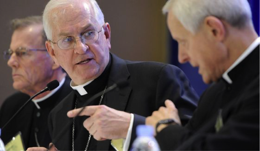 Three pale-skinned white-haired men in clerical collars—white bands beneath black shirts and suit jackets—gesture while they talk to each other in this close up shot. They are, from left, Bishop John C. Wester of Salt Lake City, Archbishop Joseph E. Kurtz of Louisville, KY and president of the US Conference of Catholic Bishops, and Cardinal Donald W. Wuerl, Archbishop of Washington. The picture was taken during the conference's annual fall meeting in Baltimore on Monday, November 10, 2014. IMAGE CREDIT: AP Photo/Steve Ruark.